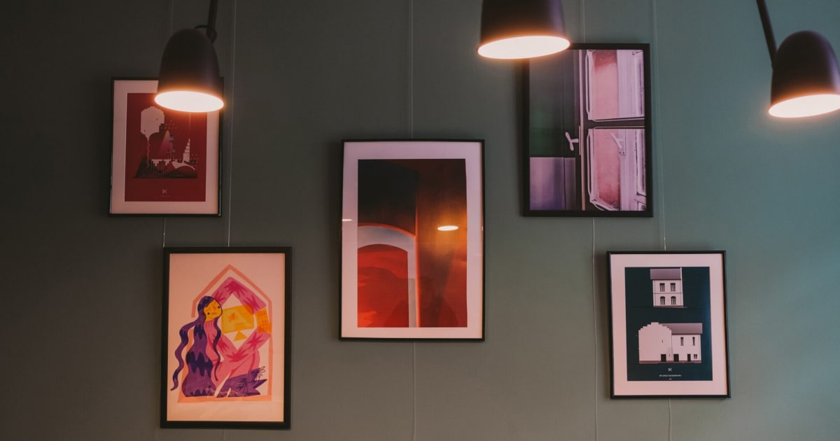 Paintings on the wall with lights from the top